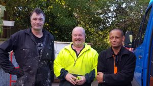 This is the team of guys working on a large decluttering project.